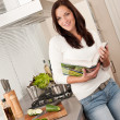 Young woman reading cookbook in the kitchen — Stock Photo #4696319