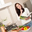 Young woman reading cookbook in the kitchen — Stock Photo #4696321