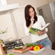 Young woman reading cookbook in the kitchen — Stock Photo #4696324