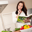 Young woman reading cookbook in the kitchen — Stock Photo #4696326
