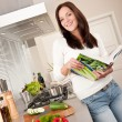 Young woman reading cookbook in the kitchen — Stock Photo
