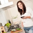 Young woman with glass of red wine in the kitchen — Stock Photo #4696334