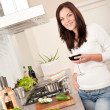 Young woman with glass of red wine in the kitchen — Stock Photo