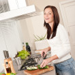 Smiling happy woman cutting zucchini in the kitchen — Stock Photo