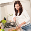 Young woman cutting bread in modern kitchen — Stock Photo