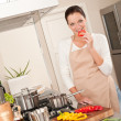 Smiling happy woman biting red pepper in the kitchen — Stock Photo #4696355