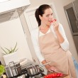 Happy woman biting red pepper in the kitchen — Stock Photo #4696358