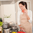 Happy woman biting red pepper in modern kitchen — Stock Photo
