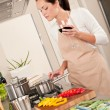 Young woman cooking in the kitchen - Stock Photo