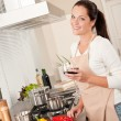 Woman with glass of red wine in the kitchen — Stock Photo #4696368