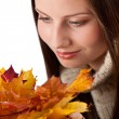Autumn portrait of beautiful woman with leaf wearing turtleneck — Stock Photo