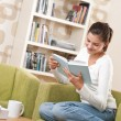 Students - Happy teenager with book sitting on armchair — Stock Photo