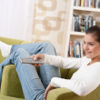 Stock Photo: Students - Smiling female teenager watching television