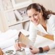 Young female interior designer at office with paint — Stock Photo #4698338