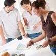 Female interior designer with two clients at office — ストック写真