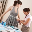 Female fashion designer measuring model for fitting — Stock Photo