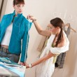 Female fashion designer measuring jacket on model — Stock Photo #4698641
