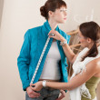 Female fashion designer measuring jacket on model — Stok fotoğraf