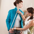 Female fashion designer measuring jacket on model — Stockfoto