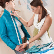 Female fashion designer measuring jacket on model — Stock Photo #4698645