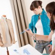 Fashion model trying turquoise jacket in designer studio — Stock Photo #4698648