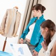 Fashion model trying turquoise jacket in designer studio — Stock Photo #4698649