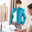 Fashion model trying turquoise jacket in designer studio — Stock Photo #4698651