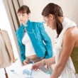 Fashion model trying turquoise jacket in designer studio — Stock Photo