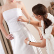 Fashion model fitting white wedding dress by designer — Stock Photo