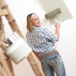 Home improvement: Blond woman painting wall — Stock Photo