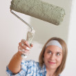 Home improvement: Smiling woman with paint roller — Stock Photo