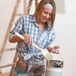 Home improvement: Smiling woman with paint and brush painting wa — Stock Photo #4698783