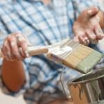 Home improvement: Woman holding paint brush — Stock Photo