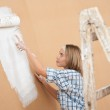 Home improvement: Woman painting wall — Stock Photo