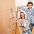 Home improvement: Young couple painting wall — ストック写真 #4698851