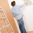Home improvement: Young man with paint roller — Stock Photo