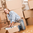 Moving house: Happy woman unpacking box — Stock Photo