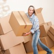 Moving house: Woman holding big carton box — Stock Photo