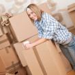 Royalty-Free Stock Photo: Moving house: Woman with box in new home
