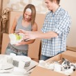 Stock Photo: Moving house: Young couple unpacking kitchen dishes