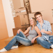 Moving house: Happy man and woman celebrating - Stock Photo