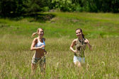 Two young woman jogging in a meadow — Stock Photo