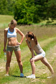 Two young women exercising in a meadow — Stock Photo