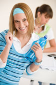 Student at home - smiling woman with bottle of water — Stock Photo