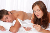 Young couple lying down in bed — Stock Photo