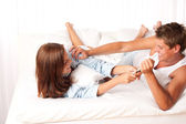Young woman and man having fun in bed — Stock Photo