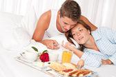 Mutlu bir adam ve kadın yatakta birlikte kahvaltı ediyor — Stok fotoğraf
