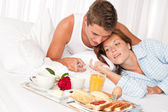 šťastný muž a žena spolu s snídaně v posteli — Stock fotografie