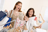 Fashion shopping - Two Happy woman choose sale clothes — Stock Photo