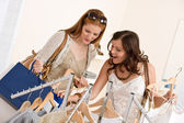 Fashion shopping - Two Happy woman choose sale clothes — Stok fotoğraf